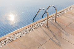 Steel ladder of swimming pool and sunlight reflection in summer Stock Image