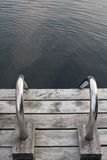 Steel ladder on wooden dock Royalty Free Stock Photo