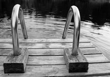 Steel ladder on wooden dock. Closeup of a steel ladder on a wooden dock leading into a northern lake black and white Stock Photo