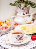 Porcelain cup of tea with lemon and sweets Royalty Free Stock Photography