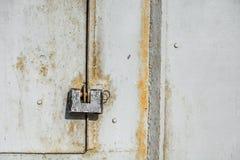Steel lock on the rusty grey metal door. close-up. Stock Photography