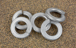 Steel lock washers on sandpaper. A small group or steel lock washers on a piece of coarse sandpaper Royalty Free Stock Photo