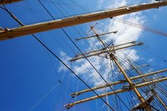 Steel masts of a sailing ship. Steel masts of a sailing ship with the lowered sails with blue sky on the background royalty free stock photography