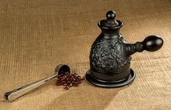 A steel measuring spoon with clay coffeepot. A steel measuring spoon with roasted coffee beans and a made of black clay coffeepot on a coarse canvas background Royalty Free Stock Image