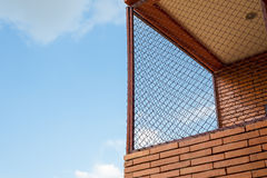 Steel mesh at balcony with brown brick wall. And blue sky stock photo