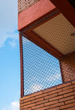 Steel mesh at balcony with brown brick wall. And blue sky royalty free stock photo