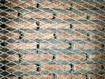 Steel mesh and brick wall. Two layer of steel mesh and brick wall texture stock photos