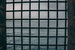 Steel mesh grid window in a castle looking out at the sea royalty free stock image