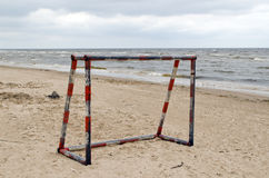 Steel metal football goal gate on sea sand Royalty Free Stock Image