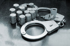 Steel metallic handcuffs and coins Royalty Free Stock Photography