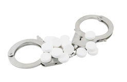 Steel metallic handcuffs and tablets Stock Photo