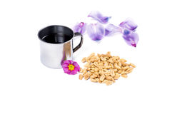 The steel mug and handful of a peanut decorated with flowers Royalty Free Stock Photography