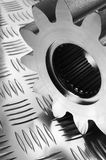 Steel-part concept. Large gear, cog on patterned stainless-steel Stock Images