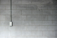 Steel pipe electric wire and plug on loft style cement wall back Stock Image