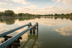 Steel pipe in the park. Steel pipe connect from pump into the lake within public park stock photography