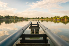 Steel pipe in the park. Steel pipe connect from pump into the lake within public park Stock Photos
