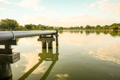 Steel pipe in the park. Steel pipe connect from pump into the lake within public park Stock Photo