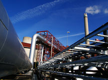 Steel pipelines and smokestack on blue sky Stock Photos