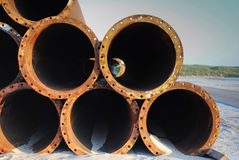 Steel pipes on beach. H to supply sand stock photo