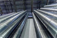 Steel pipes, parts for construction of ducts of industrial air condition system in warehouse. Bottom view.  Royalty Free Stock Image