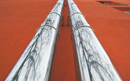 Steel pipes on a red wall Stock Photo