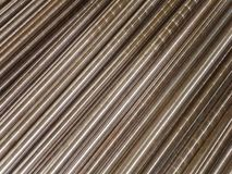Steel pipes and rods laid parallel to diagonal. Industrial abstract background. Stock Photo