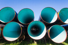 Steel Pipes Stacked. Large steel water pipes stacked ready for construction of a new water line infrastructure.Close up wide angle photo image in front of the Stock Photo