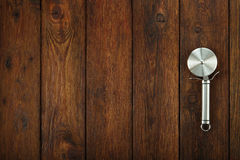 Steel pizza cutter at wooden background Stock Image