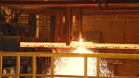 Steel Plant. Gas burner cuts the moving metal beam stock footage