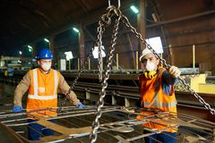 Steel Plant Workers Using Lifting Beam. Two young workers of steel plant wearing uniform and filter masks using lifting beam in order to move heavy sheet metal stock image