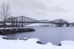 The 1919 steel Quebec Bridge with the longest cantilever span in the world. Seen from the south shore St-Romuald sector of Lévis during a grey winter day, Qu royalty free stock photos
