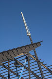 Steel Rafter Construction. Steel rafters are lifted into place by a white crane Stock Photos