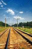Steel Railroad Tracks. Old Steel Railroad Tracks with reflection under bkue sky anf clouds Stock Photo