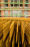 Steel reinforcement. A stack of reinforcement steel mats with a green scaffolded old factory building. With space for copy stock images