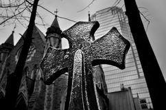 Steel religious cross on skyscraper background black and white Stock Photography