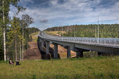 Steel road bridge on concrete supports, crosses forest stream. Stock Photos