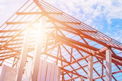Steel roof frame structure of building house. At construction site with blue sky clouds and sun light stock photo