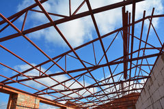 Steel roof trusses details with clouds sky background. Roof-trusses. Royalty Free Stock Photos