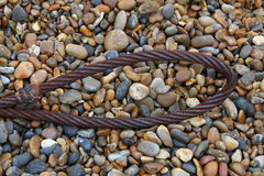 Steel Rope. A study of a steel rope on a pebble beach Stock Image