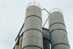 Steel round storage tanks or storage compartment. At background of cloudy sky Stock Photos
