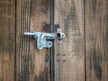 Steel rusty metal latch lock hanging outdoors on wooden double door. Steel rusty metal latch lock hanging outdoors on a wooden double door royalty free stock images