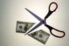 Steel Scissors Cutting in Half a 100 Dollar USA Bill royalty free stock photos
