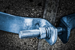 Close-up of a metal bolt shaft with spiral thread and hexagon nut on a concrete pole. Steel bolted joint with blue hoop on dark gray background. Idea of cohesion stock image