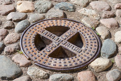 Steel sewer manhole on the cobblestone road Stock Image