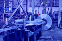 Steel sheet is wound on a roll on a special machine Royalty Free Stock Photo