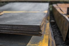 Steel sheets deposited in stacks in packs at the warehouse of metal products. Weathered metals sheet for construction royalty free stock image