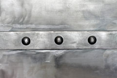 Steel shiny plate, with a horizontal strip, connected by rivets Royalty Free Stock Photography