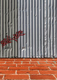 Steel Siding Background. Composite image of a brick sidewalk next to a galvanized steel siding building. Small graffiti placed on wall with font reads sup doc Stock Images