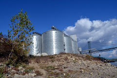 Steel silos and blue sky with clouds. Grain storage system with corrugated steel storage bins and grain distribution system on the background of sky with clouds stock photography