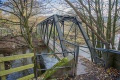 Steel span footbridge crossing a river Royalty Free Stock Images